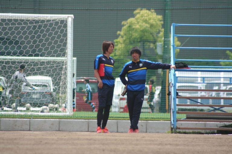 談笑するフロンターレU-12の佐原秀樹監督と育成プロジェクトグループの吉田勇樹コーチ