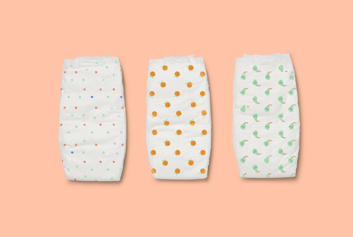 3 patterned Tooshies by Tom nappies on an orange background