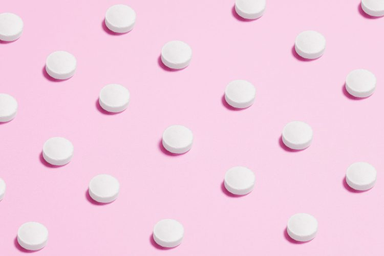 white-round-capsule-on-pink-background-close-up-photography-3683047-min