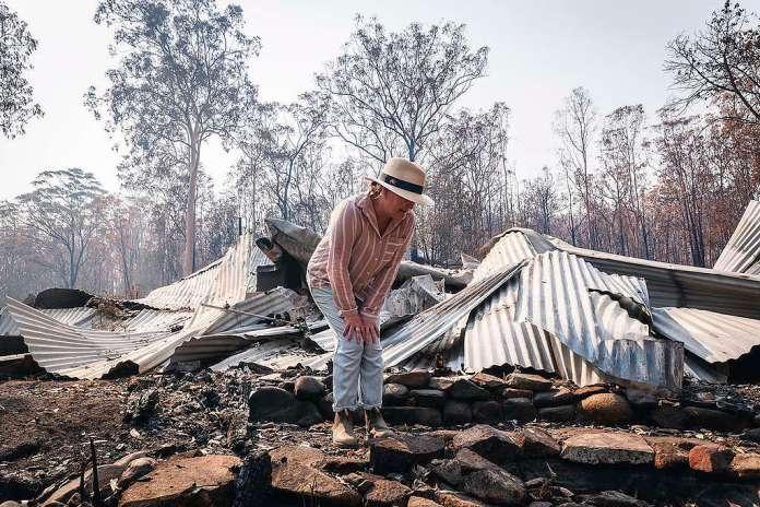 Melinda Plesman, která přežila požár, zkoumá škody na svém domově v obci Nymboida v Novém jižním Walesu. © Natasha Ferguson / Greenpeace