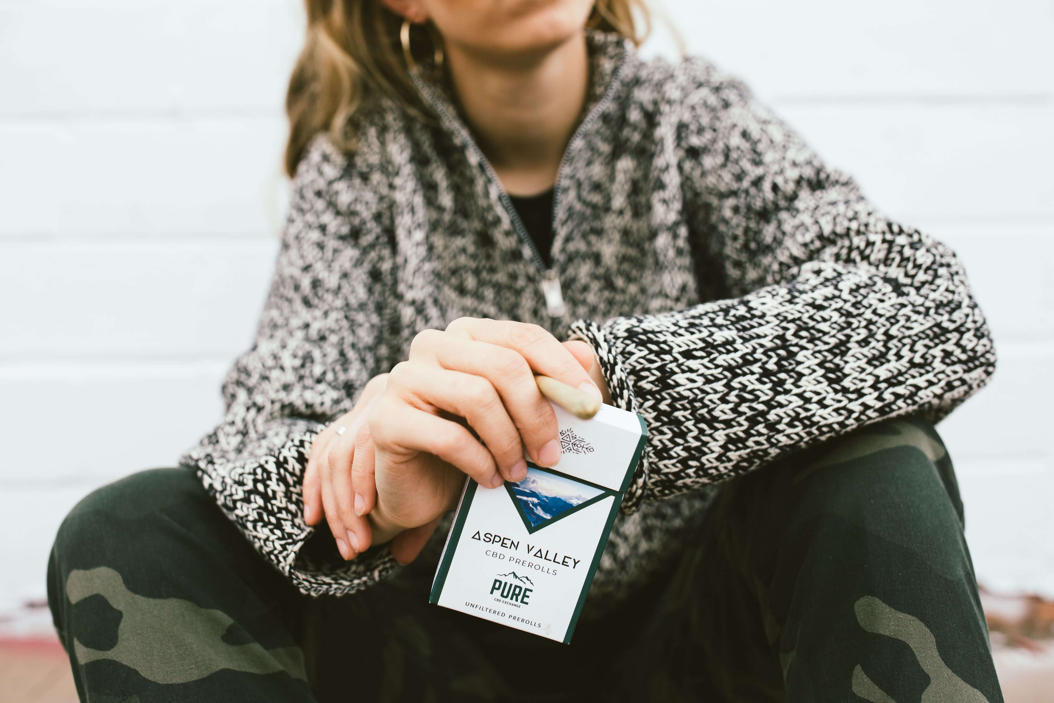 Girl sitting holding a pack of CBD Joints