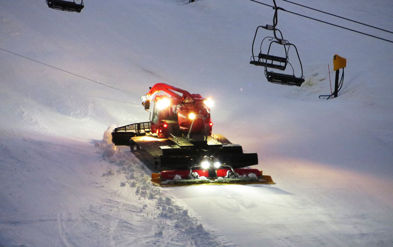 a piste basher grooming the piste at night underneath a chairlift