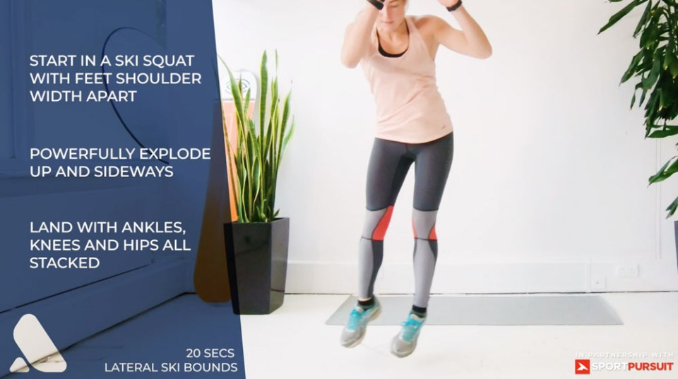 woman performs ski fitness exercise - lateral ski bounds