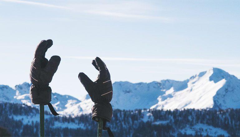 ski gloves on ski poles in front of mountain