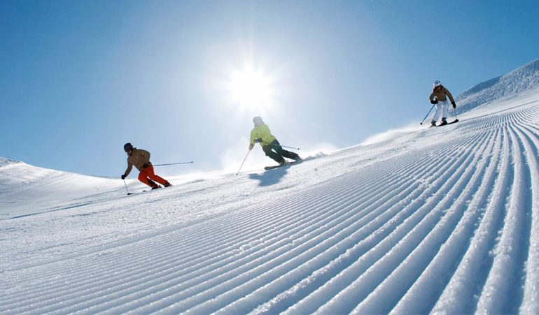 two adult skiers enjoy freshly groomed pistes during private ski lesson