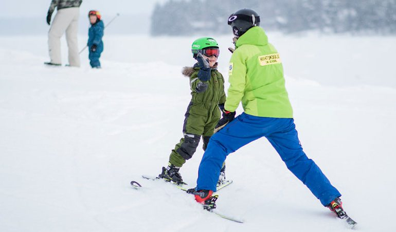 smiling child high-fives private ski instructor