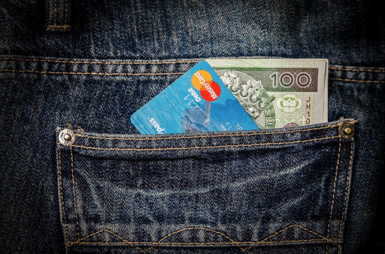 Mastercard and banknote in back pocket of jeans