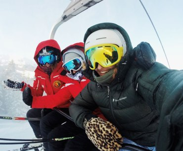 Three women skiers smiling in chairlift selfie photo