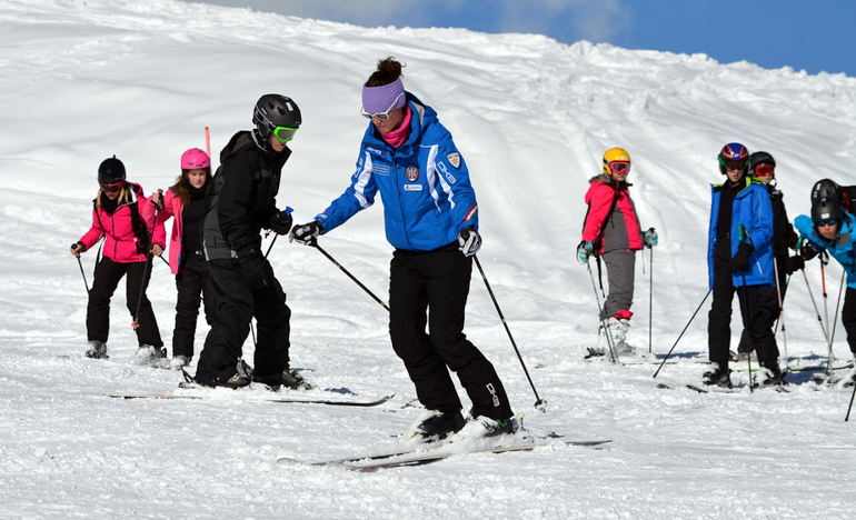 female ski instructor teaches group ski lesson