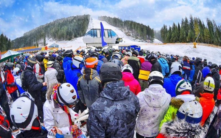 many people in colourful clothing in long line ups for the chairlift