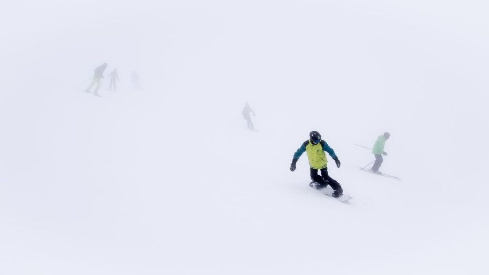 Whiteout: Skiers and snowboarders in thick fog on ski slope in ski resort.