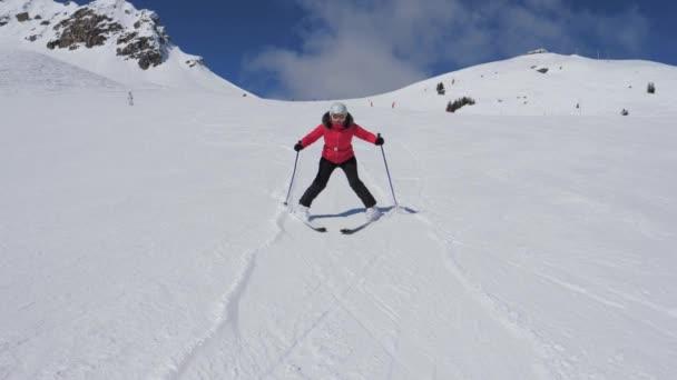 Woman snowplows on skis