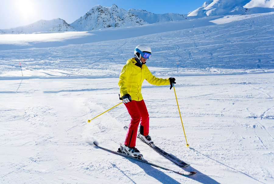 Woman in yellow jacket snowplough skiing