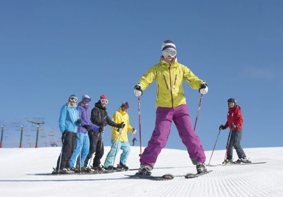 Woman have beginner group ski lesson