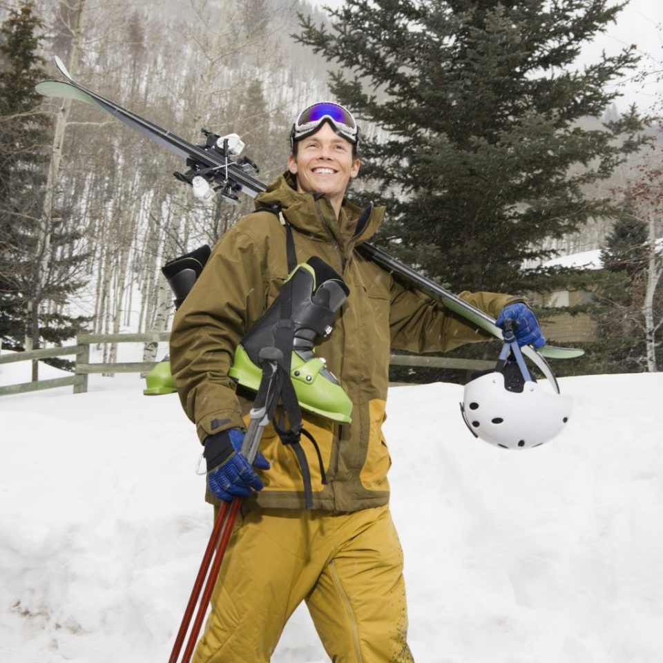 Attractive man in winter clothing walking in snow carrying ski equipment and smiling.