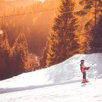 Child on drag ski lift at sunset