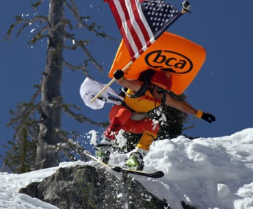 Shane McConkey dressed as Saucer Boy jumps off cliff holding American flag