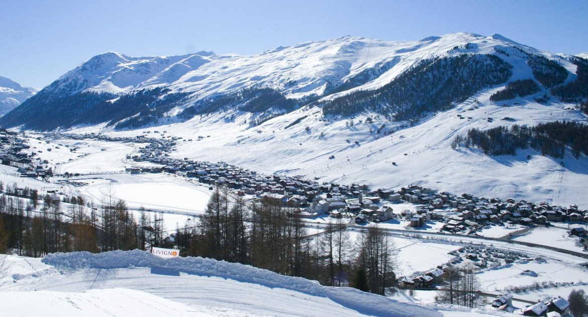 The village of Livigno nestled in underneath the tree-lined ski slopes of the mountains above.