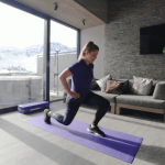 A woman in purple and black gym clothes performs a lunge as part of an at home ski workout