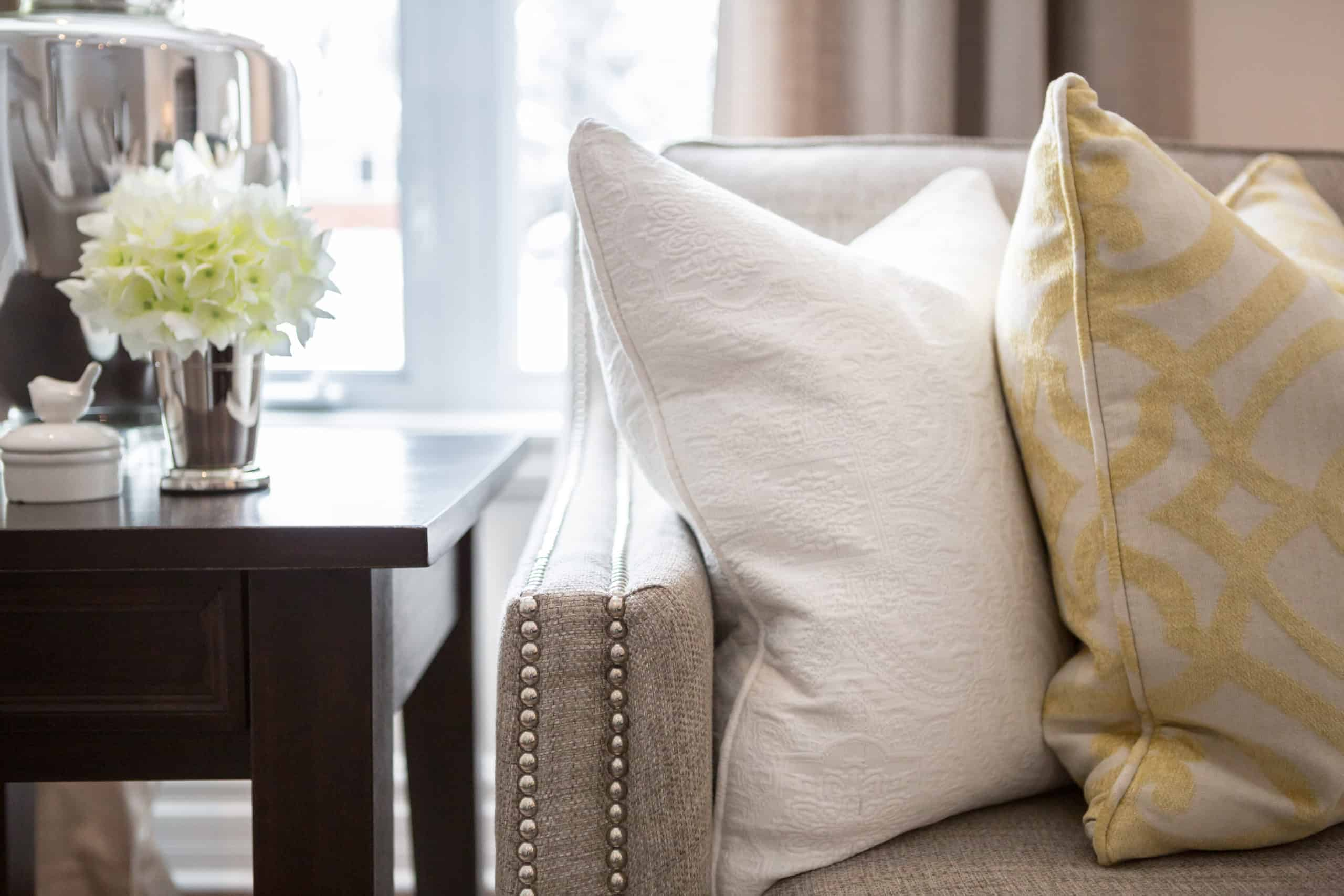 End of a couch with white and yellow pillows