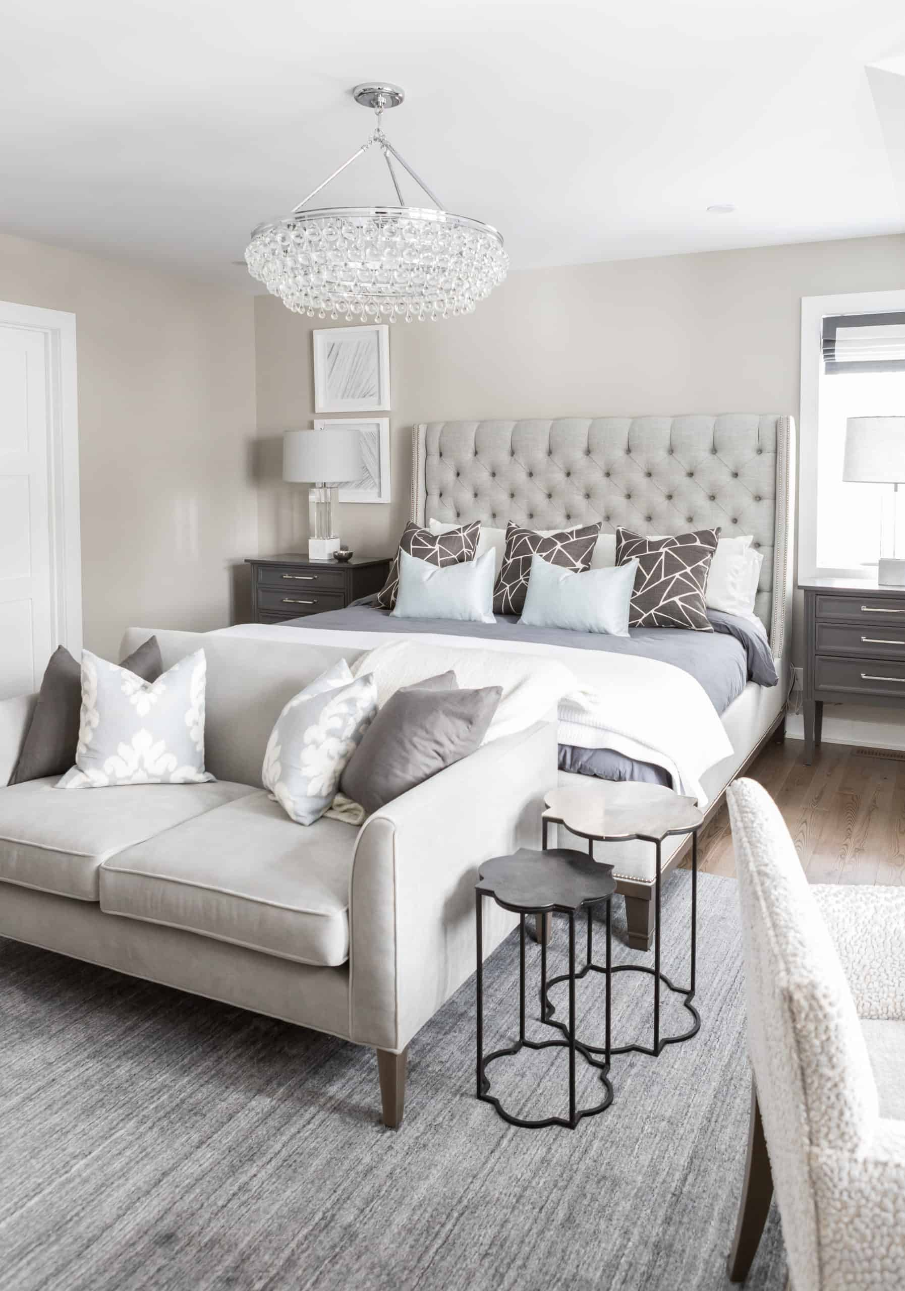 Fancy chandelier above a large gray gray bed