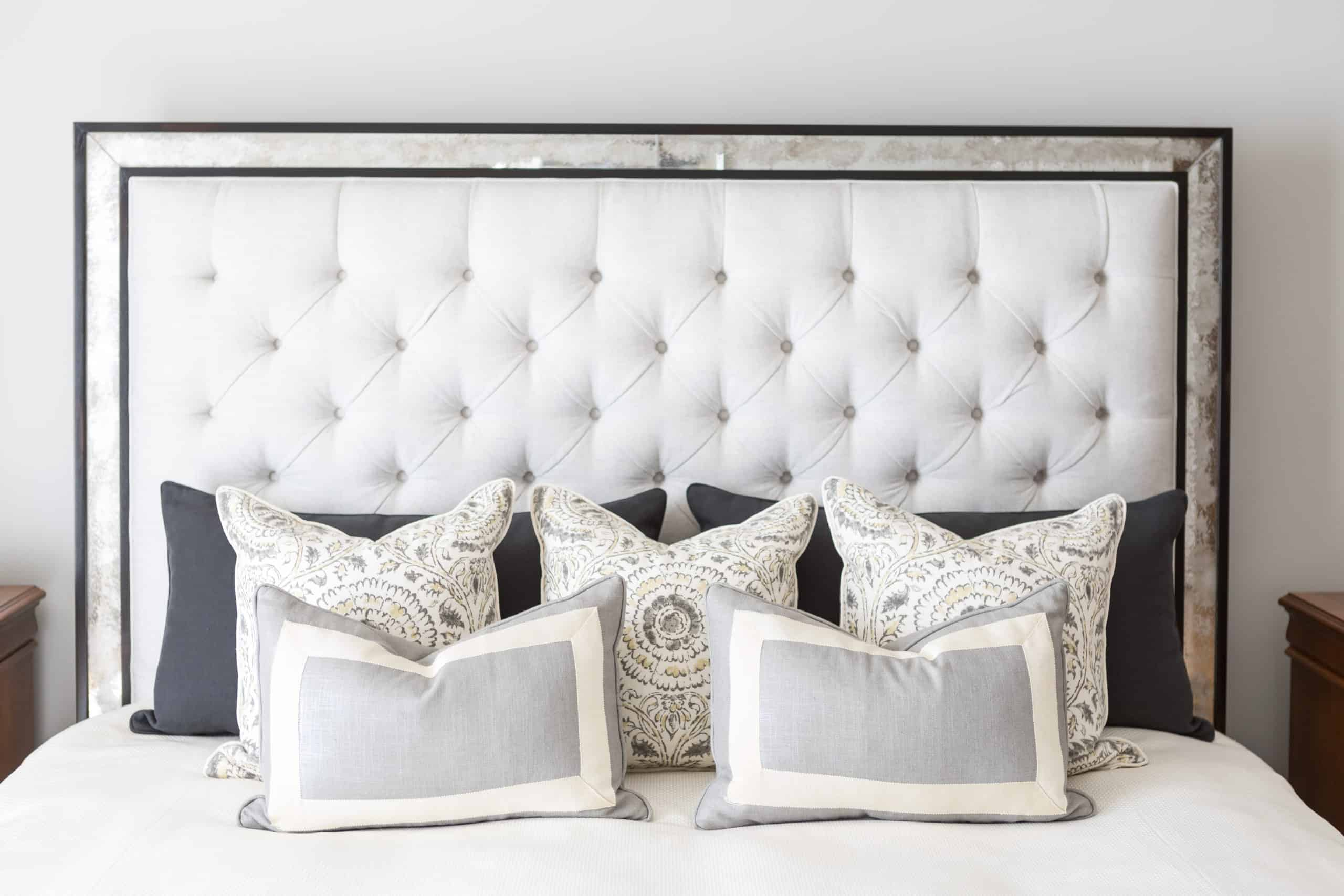Array of patterned pillows on a bright white bed