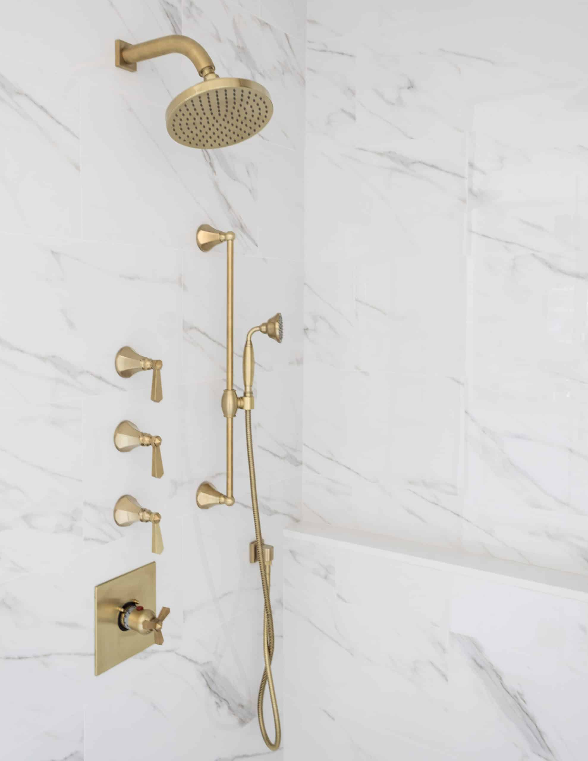 Golden shower faucet on a marble wall