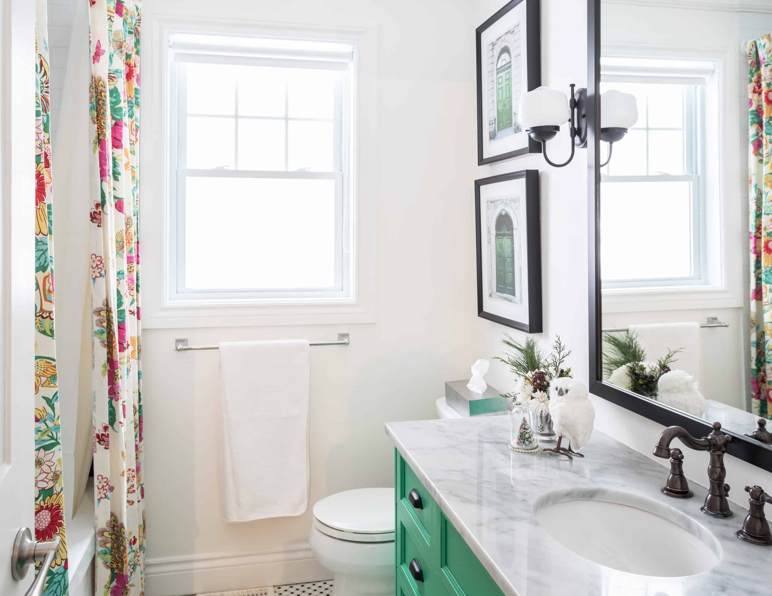 Teal vanity with a marble countertop inside a clean bathroom