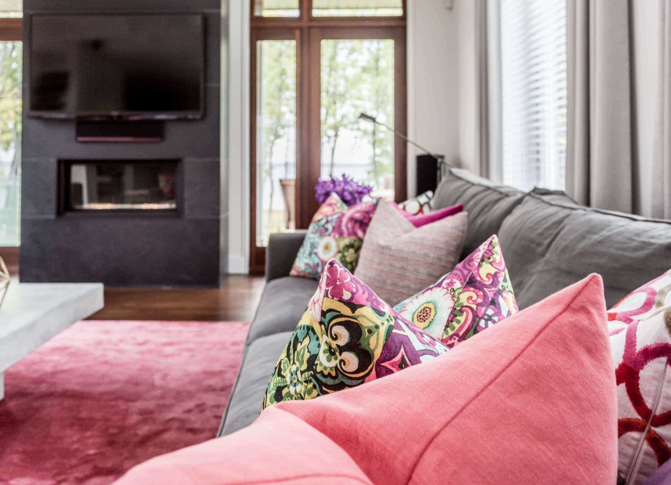 Gray couch with colorful pillows on it