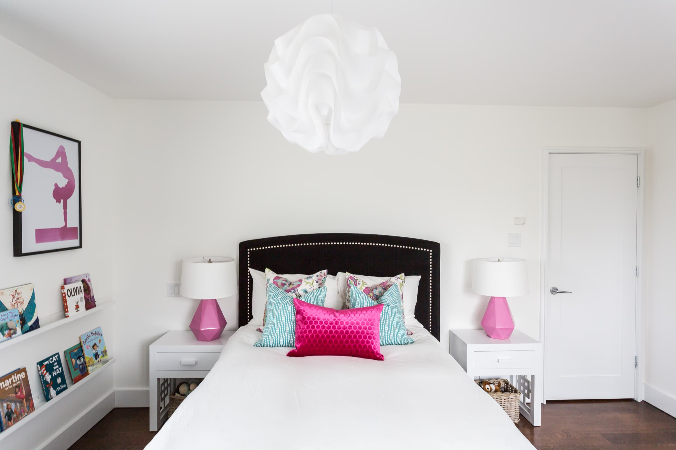 Large bed with an array of colorful pillows on it