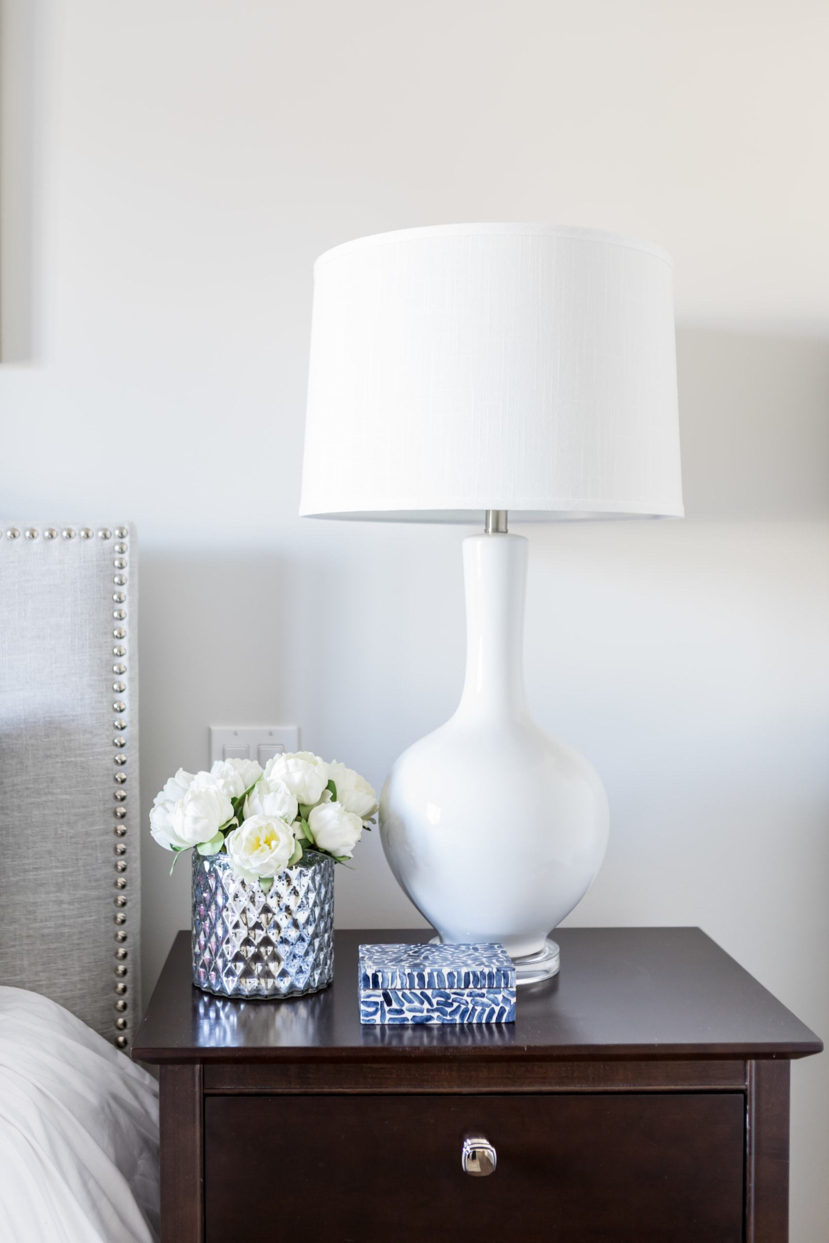 White lamp on a dark bedside table