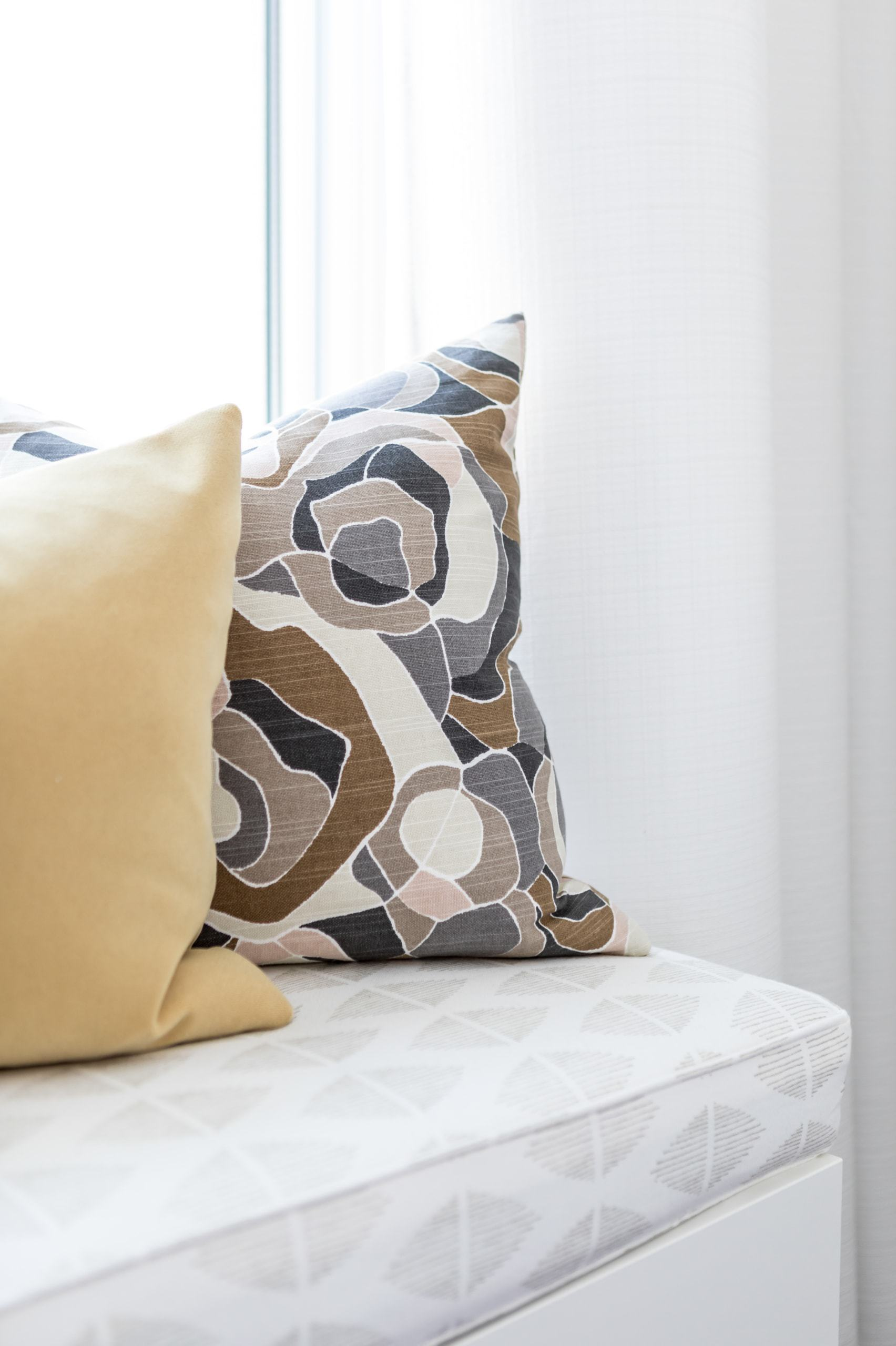 Brown patterned pillow near the window
