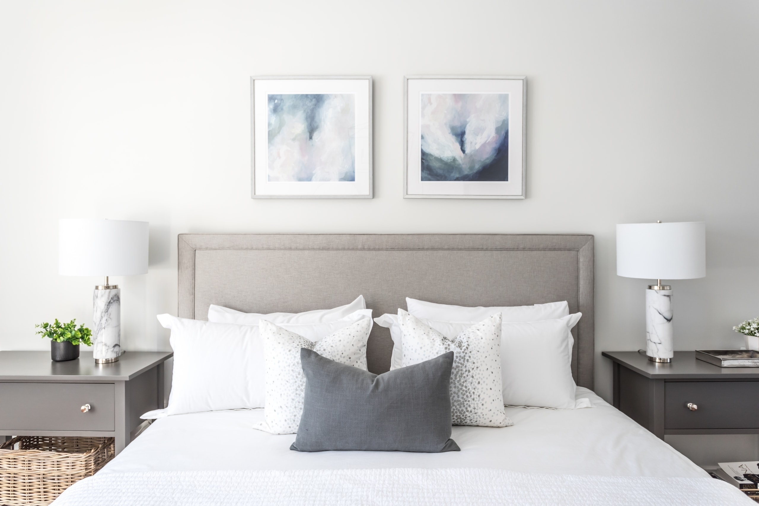 Triangle of pillows going dark to light on a large bed