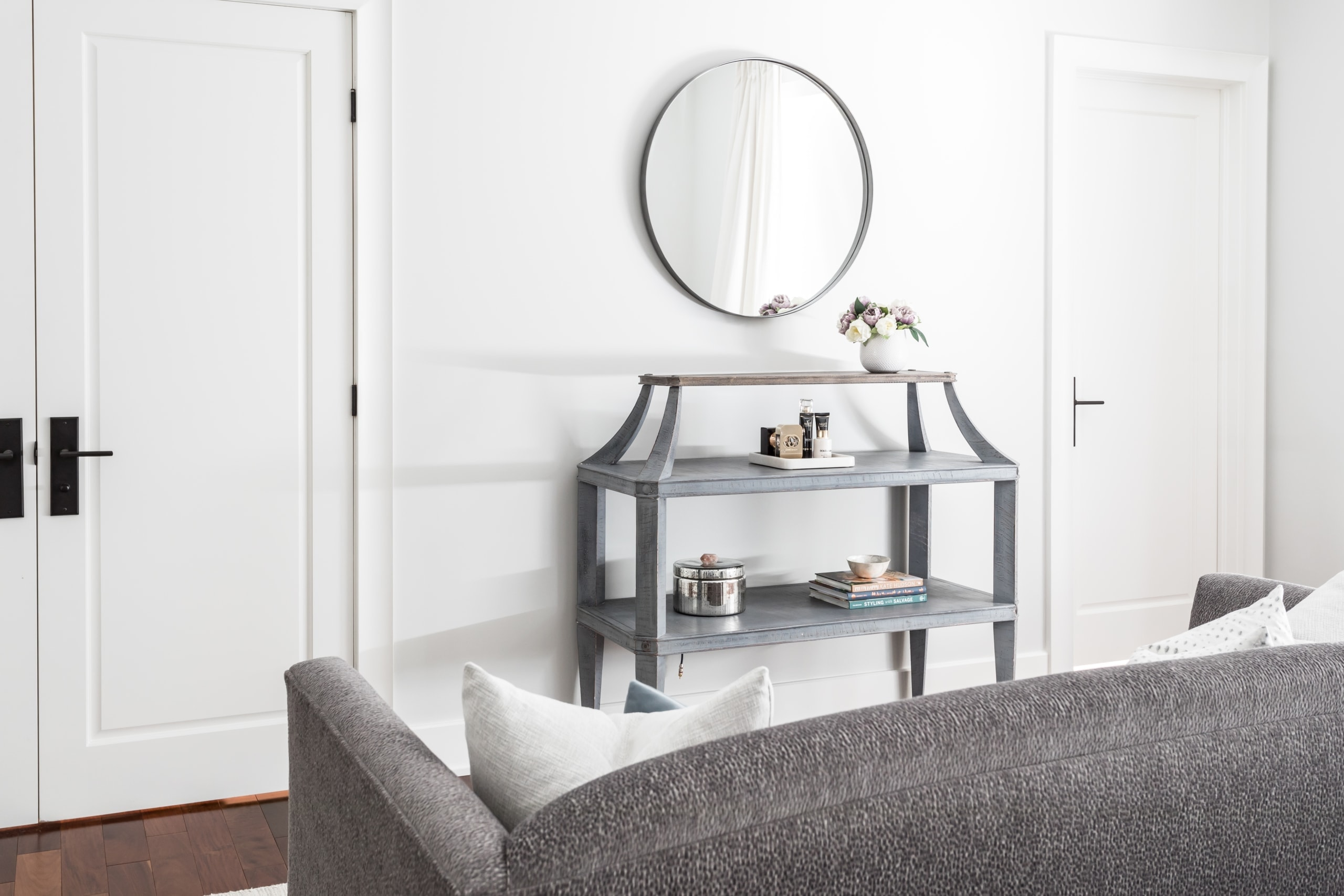 Small couch facing a shelving unit with an assortment of decorations on it