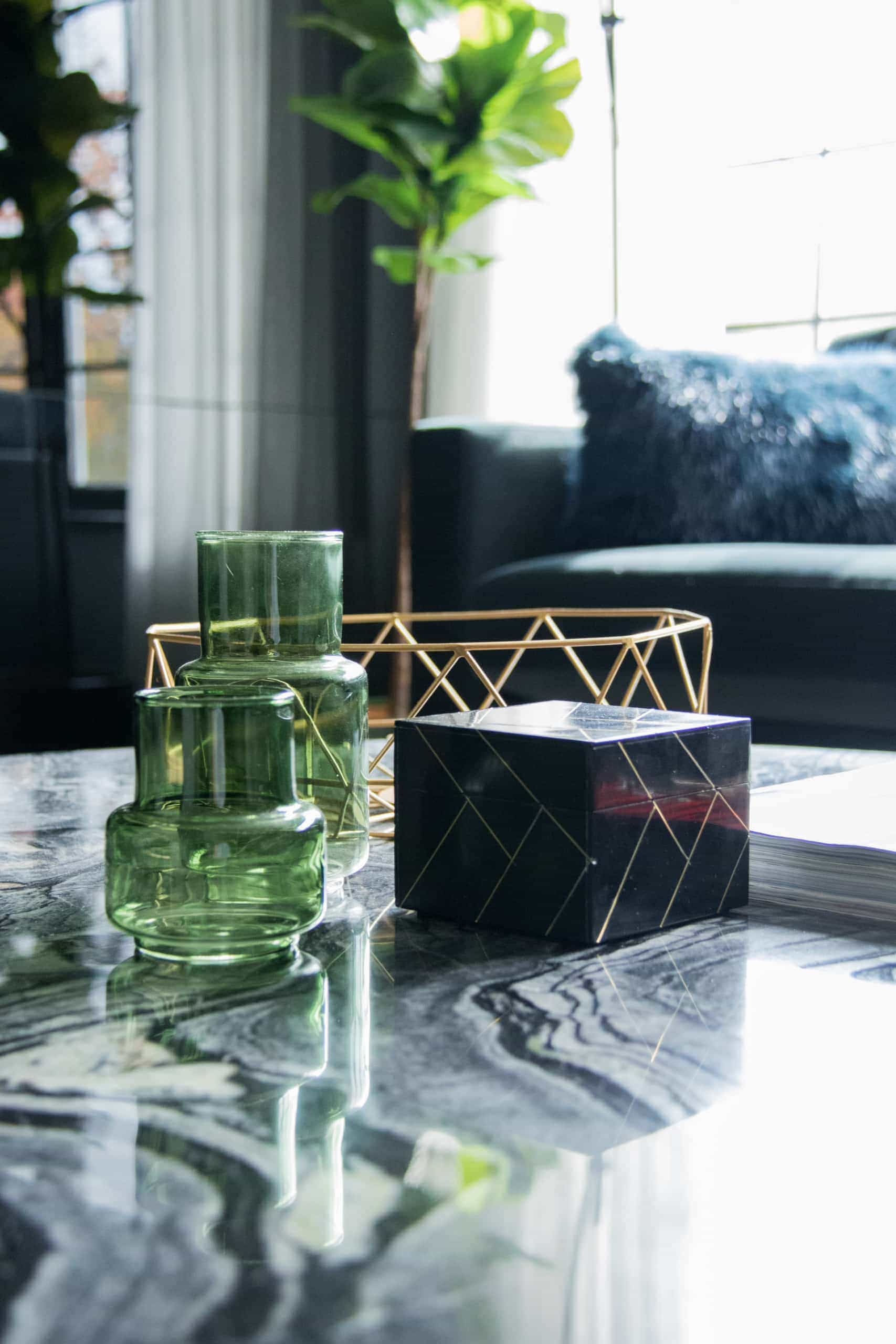 Green, glass pots on a gray coffee table