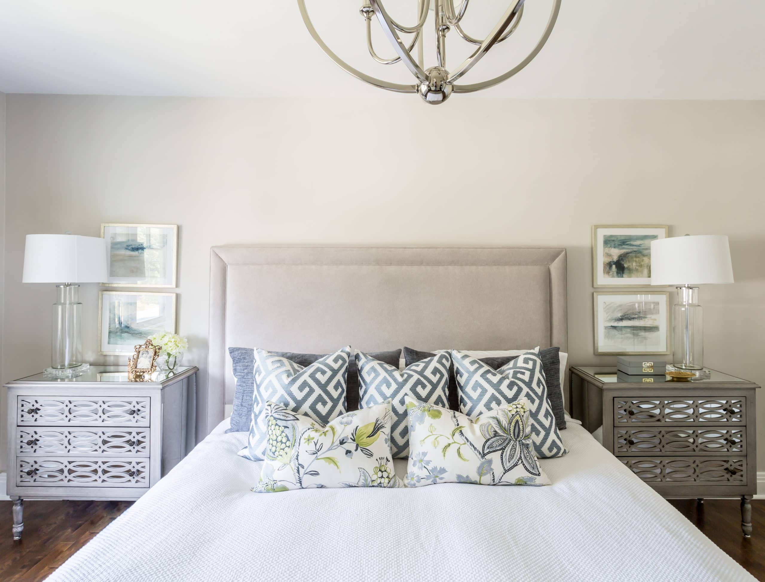 Large, white bed within a master bedroom with nightstands on each sides