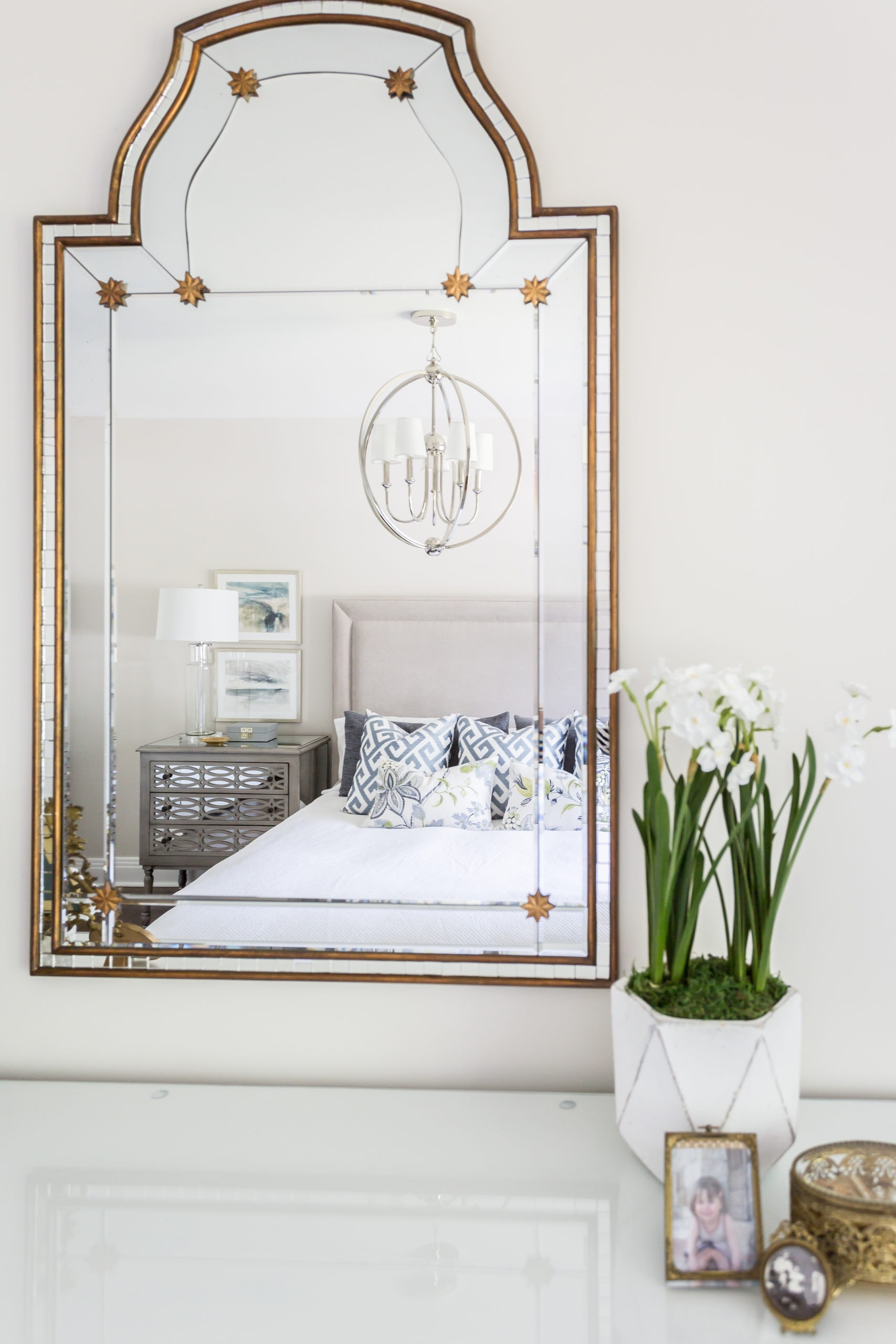 Mirror within master bedroom reflecting the bed
