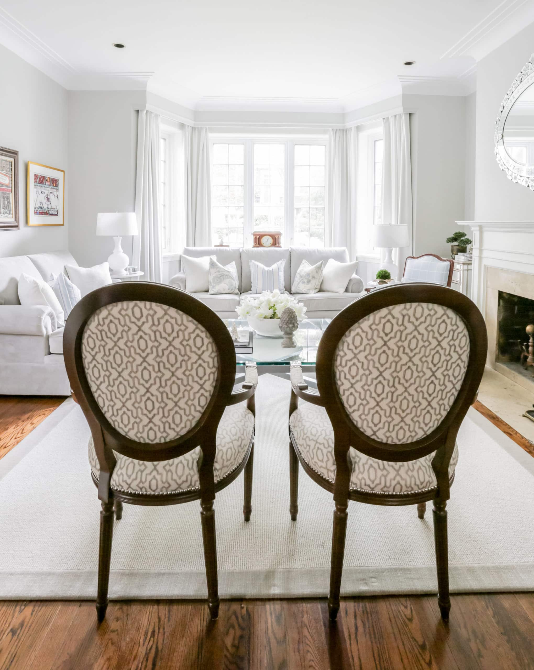 Large, bright living room with a focus on the back of a couple small chairs