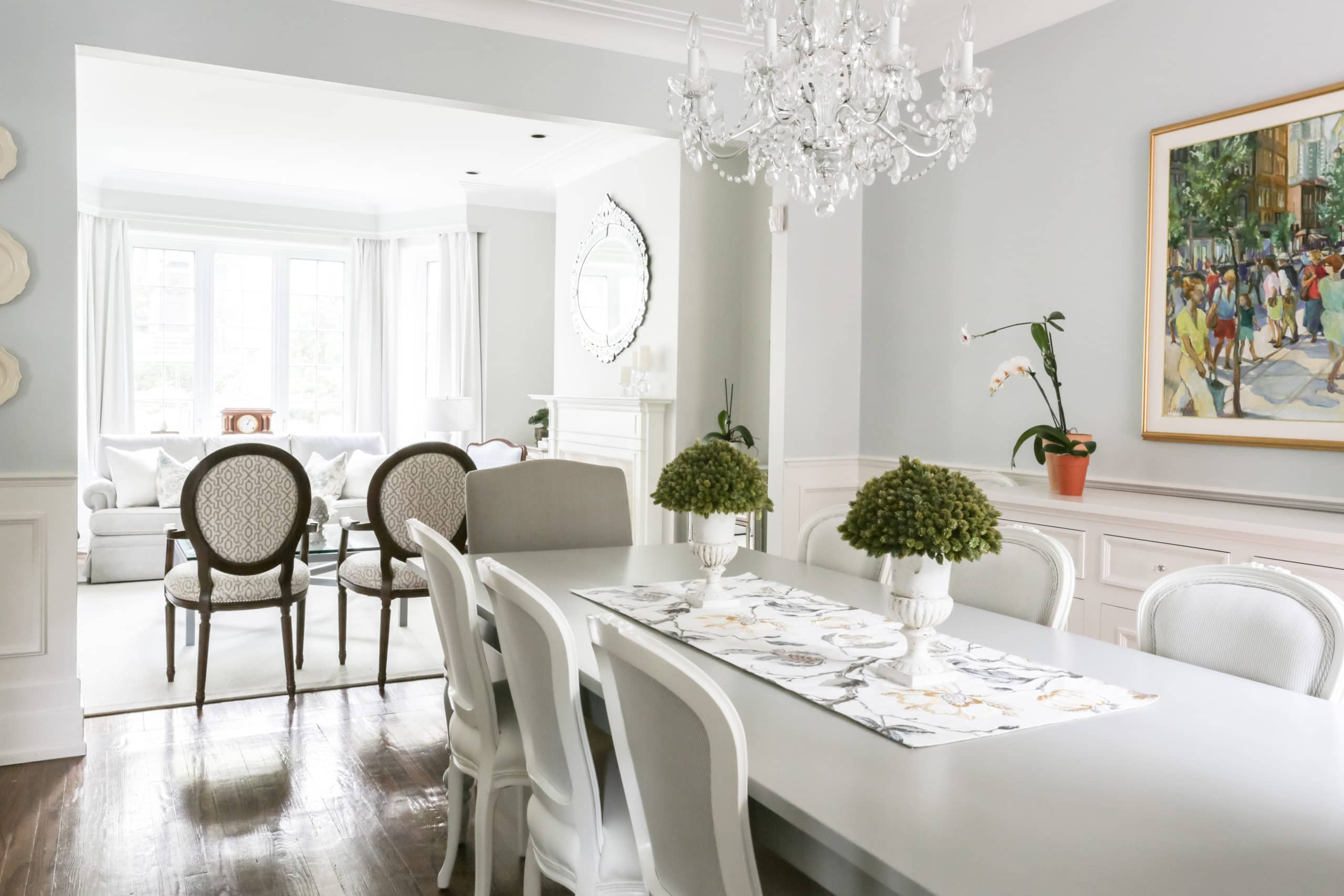 Bright dining room with a large rectangular table with a small fancy chandelier above it