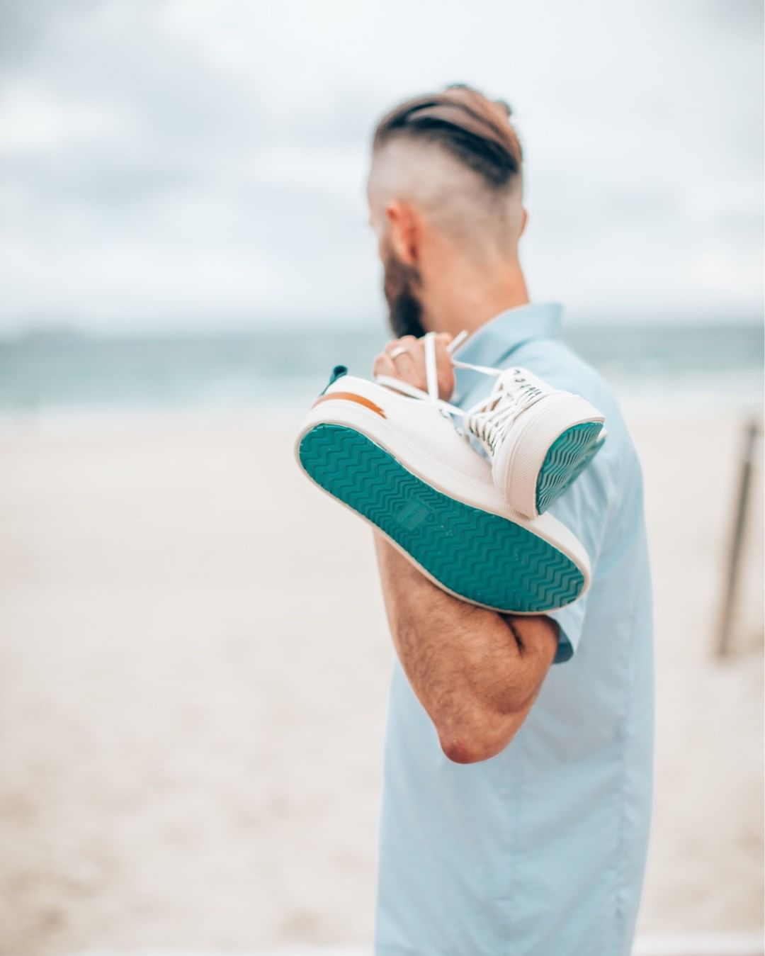 Michael Checkers holding TOMS sneakers on South Beach facing the water