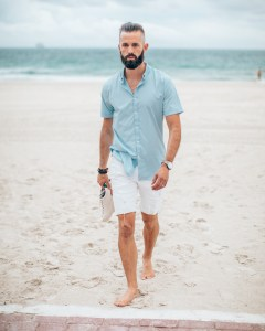 Michael Checkers summer street style fashion photo in South Beach Miami holding shoes on the beach walking onto the brick path