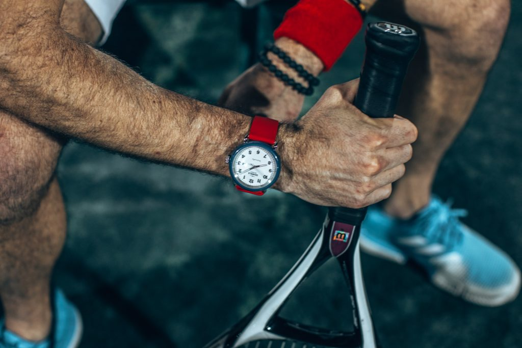 Michael Checkers wearing a Shinola Detrola Ace watch on a tennis court in Miami from above point of view