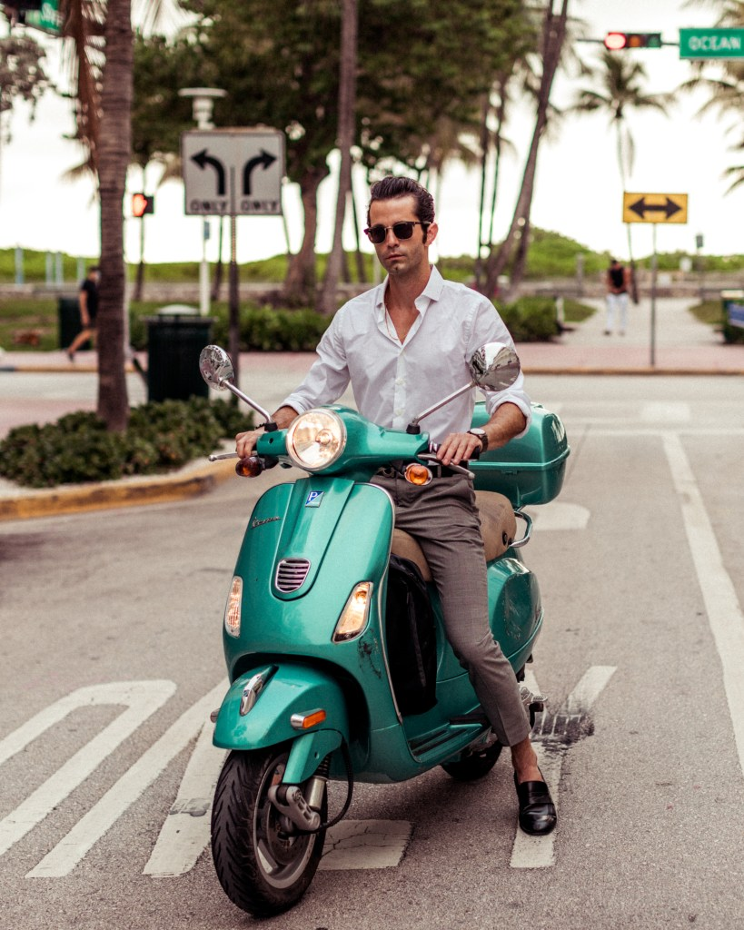 Michael Checkers wearing Express Men in Miami Beach on a Vespa