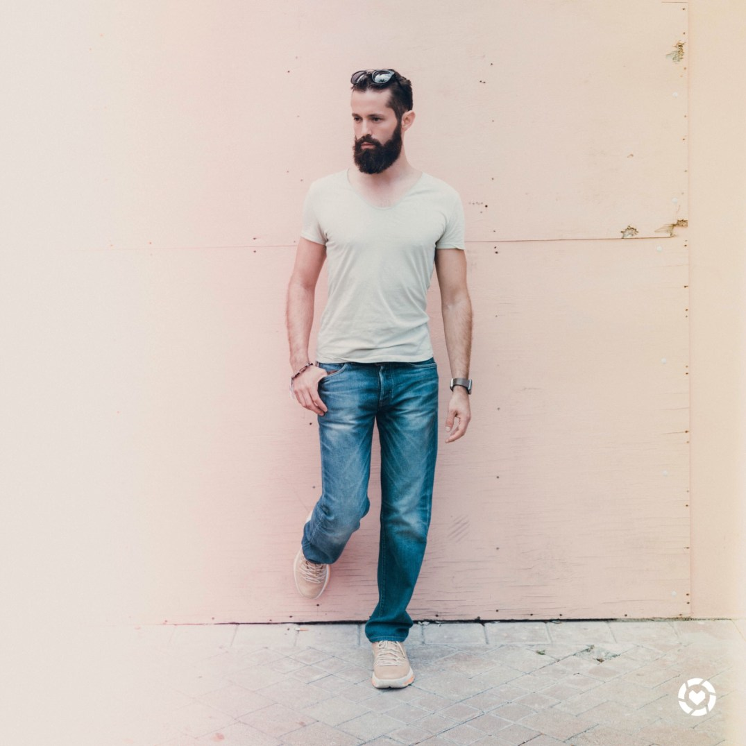 Men's Streetwear Look 010 acid wash jeans and light scoop neck t-shirt on a pink wall