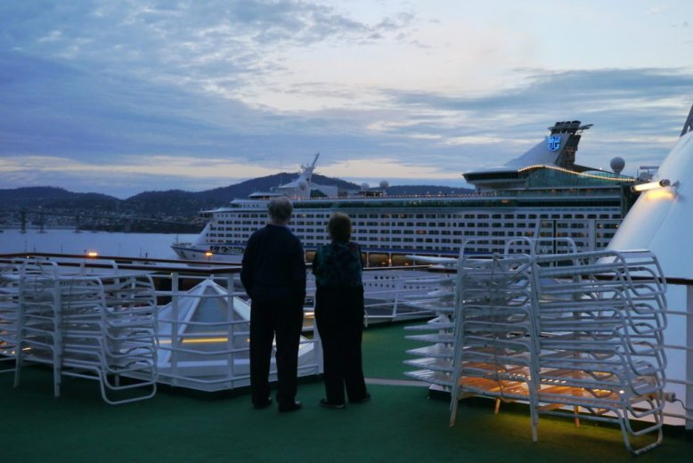 Two passengers overlooking a second ship in harbour