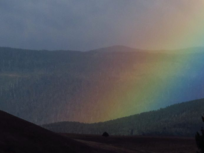 A bright distant rainbow fills the picture frame when a zoom camera lens is used