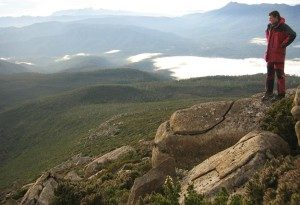 A climber admires the view on the dolerite summit of Mt. Picton, Southwestern Tasmania