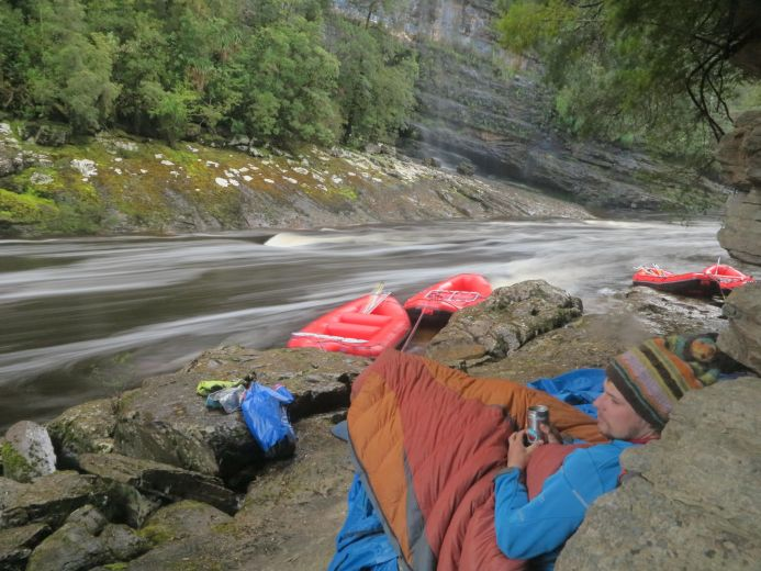 The guide rests at a sheltered campsite