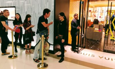 Tourists are queuing in front of a luxury outlet in Bangkok