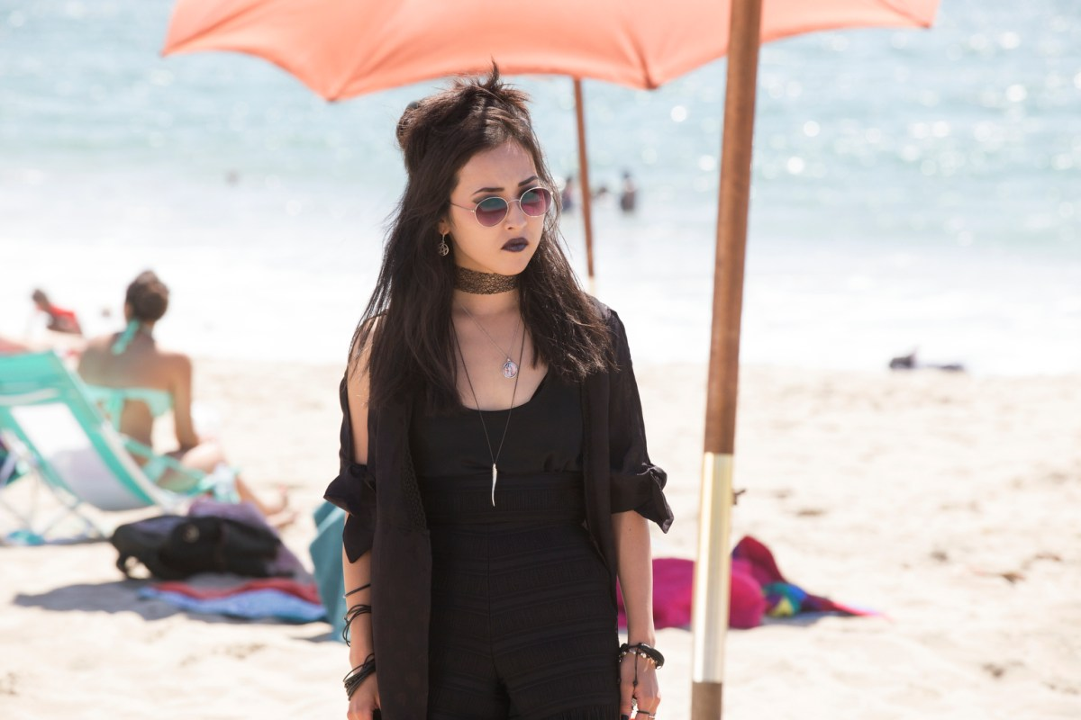 nico wears all black on the beach